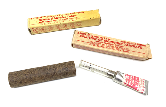 Illustration showing Item No. 9775700; Morphine Tartrate, 1 Tube with different designs of outer box. The hard fibreboard tube was used to protect the Syrette in certain types of First-Aid Kits (notably the Parachute First-Aid Packet – Item No. 9778500).