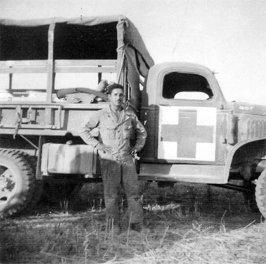 Driver J. D. Lloyd poses for the camera in front of a 2 1/2-ton Truck assigned to the 11th Evacuation Hospital. Of interest is the large Geneva Convention markings which have been applied to the door of the vehicle.