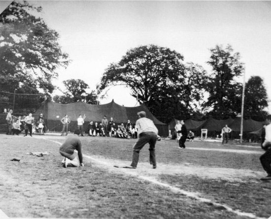 Hospital personnel engage in a friendly game of baseball during a quiet period in activities.