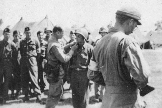 Ceremony during which Captain J. J. Belden gets promoted to the grade of Major. The  Officer is Major General Matthew B. Ridgway, CG, 82d Airborne Division. The date must be early July 1944 (J. J. Belden served from 7 May 1942 until 5 December 1945 in the Zone of Interior, Mediterranean Theater, European Theater, and eventually in Japan).