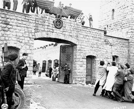 KZ Mauthausen, Austria, Prisoners pull down German eagle with swastika at the entrance of the Concentration Camp, 6 May 1945.