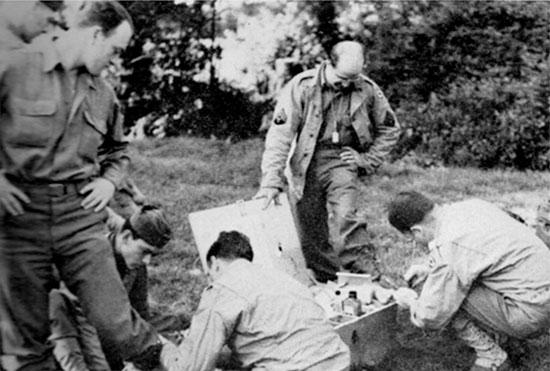 31 July 1944, Transit Area B, Utah Beach, Normandy. Hurting feet receive some treatment.