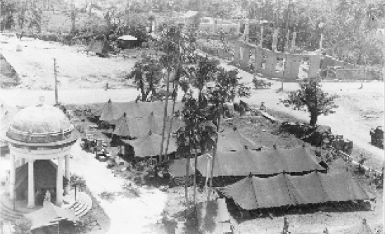 99th Evacuation Hospital operations in the plaza at Molo, Panay, Philippine Islands. Apparently taken from the damaged bell tower of Santa Ana's Catholic Church between July 31 and September 9, 1945. (First Sergeant Elmer R. Young collection).