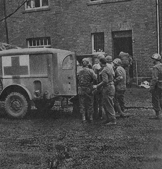 Medical personnel help patients into a 3/4-ton Ambulance for evacuation to an Army Hospital in the rear.