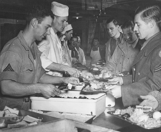 23 November 1944, GIs enjoy Thanksgiving Dinner somewhere in a barn, a requisitioned, or an abandoned building. It was always a treat to obtain some real hot chow with all the trimmings, and many a soldier ate until he got sick ... unfortunately many others had to do with cold food outside ...