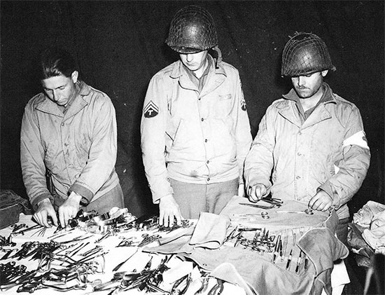 Medical personnel of the 326th A/B Med Co preparing their instruments while at Hiesville, Normandy, early June 1944.
