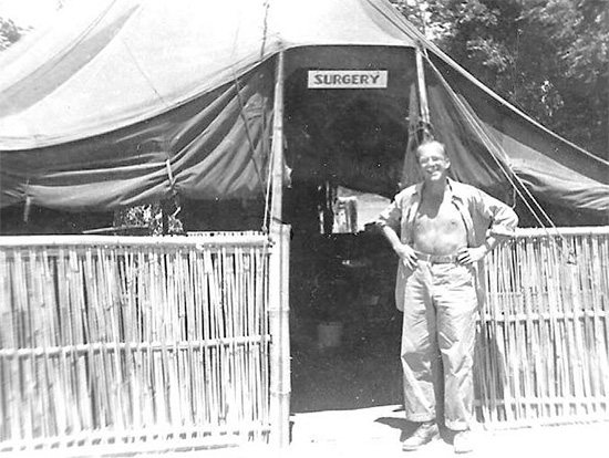 "Technician 3d Grade Glenn E. Turner, in front of the unit's ""Surgery"" tent."