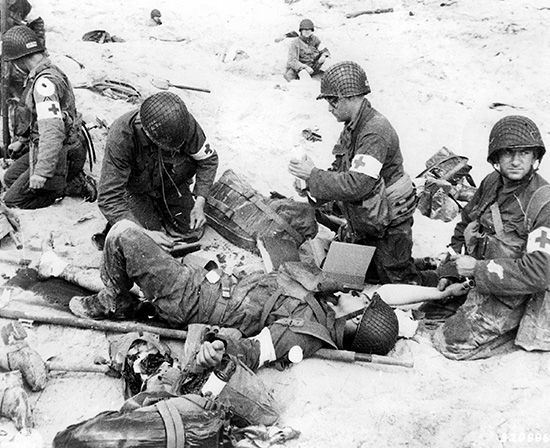 Medical personnel of the 4th Infantry Division treat a wounded fellow medic on Utah Beach. This photograph, taken on 6 June 1944, clearly shows this idiosyncratic Bag.