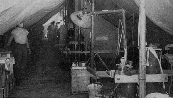 General view of an operating room set up under canvas in the field. The white cotton liners for the tents can be clearly seen.