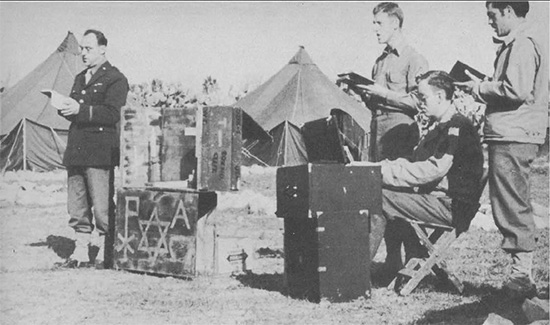 Chaplain Karl Scheufler leading a worship service at an unidentified Evacuation Hospital. Photograph taken sometime in 1944.