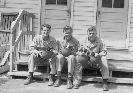 Members of the 48th Field Hospital take a break in front of one the Enlisted Men's barracks. They hold 4 new-born puppies in their liners.