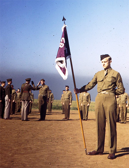 Formation, Camp White, Medford, Oregon. A Corporal holds the unit's Guidon, while the Officer saluting in the the background (left) is Major Q. Nicola, MC, O-338283, the organization's Executive Officer.