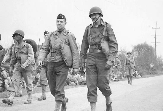 Major Quintus Nicola (R, with helmet liner) during a road march, while training at Camp White, Medford, Oregon.