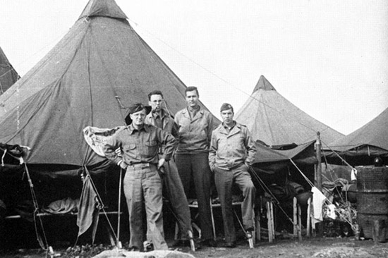 "Four members of the 45th General Hospital pose for a photograph in front of their Pyramidal Tent during the bivouac at ""Goats Hill"", en route to Naples, Italy."