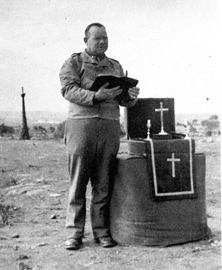 "Capt. George F. Hood, (Protestant Chaplain) conducts a service for the personnel of the 45th General Hospital during the bivouac at ""Goat Hill"""