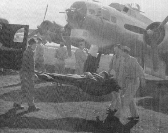 Wounded servicemen are transferred from Air Force transport to Ambulances destined for the 26th General Hospital.