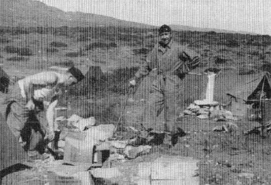Two unidentified men of the unit prepare their shelter tents and surrounding area in North Africa.