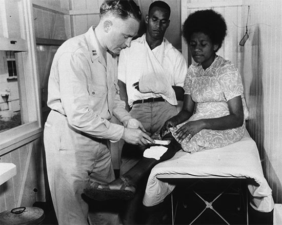 At the Out-Patient Clinic of the 71st Station Hospital in Fiji, Capt. George Warnock, MC, of Freeport, LI, treats a Fijian woman, Stery Uquaqe, for burns, as her husband, Roney, looks on.