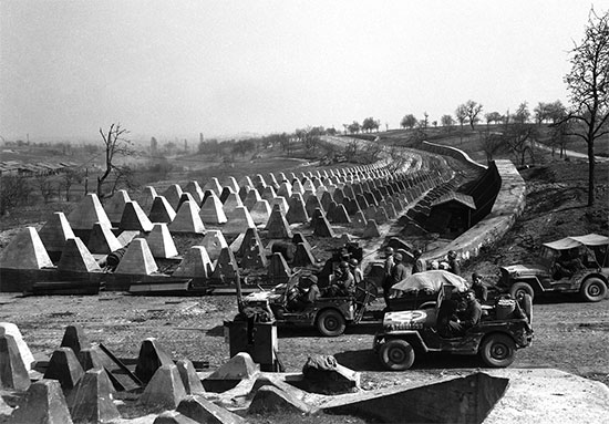 Men of the American 7th Army pour through a breach in the Siegfried Line defenses, on their way to Karlsruhe, Germany on March 27, 1945, which lies on the road to Stuttgart.