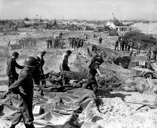 Utah Beach, June 1944. Personnel of the 1st Engineer Special Brigade bringing in a dead soldier for temporary burial.