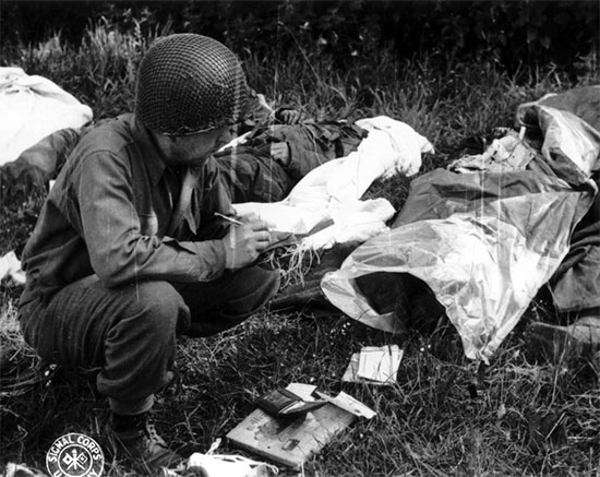 Omaha Beach, collection point, Sergeant Peter F. Slusarczyk, 603d QM GR Co, verifies and completes the EMT of a dead soldier, June 12, 1944, prior to preparation for temporary burial at Sainte-Mère-Eglise Cemetery.