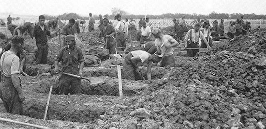 German PWs at work digging graves at the Sainte-Mère-Eglise Cemetery No. 1, Normandy, June 9, 1944.