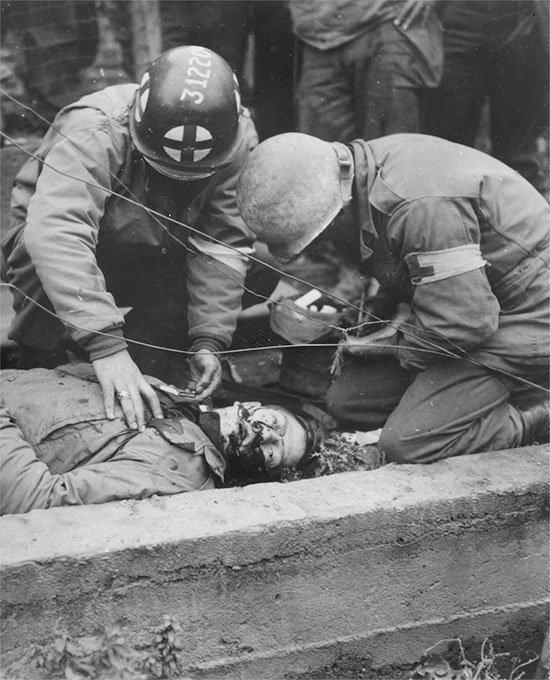 Somewhere in France 1944. First aid being applied to a wounded GI in the field, prior to evacuation.