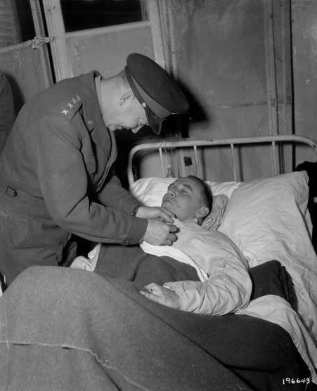 General Dwight D. Eisenhower awarding the DSC and Purple Heart to patient Colonel Dwight T. Colley, November 15, 1944, during the 12th Evacuation Hospital's stay in Nancy, Lorraine, France.