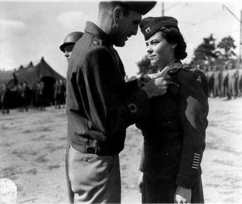 Colonel George McCoy, Commanding Officer, 12th Evacuation Hospital, awards the Legion of Merit to Captain Lillian Carter, ANC Chief Nurse, July 29, 1945, during formation and parade, somewhere in Germany.