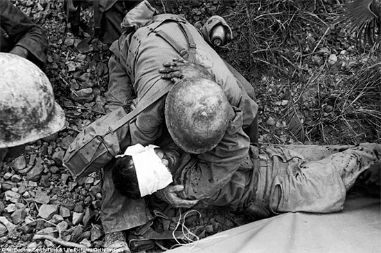 1943; somewhere  in the South Pacific Area. Medical Department personnel comfort a wounded soldier.