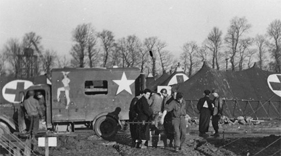 "Picture of ""Beached Bessie"", a former French ambulance used by the Germans, gift of a US Officer to the ARC. Quite heavily decorated (paintings removed by order of the CO), the vehicle first served as a transport for the American Red Cross contingent, but was later taken over by the 25th General Hospital for use as a mess truck to carry the food to the different wards, being christened ""Meals on Wheels"". This vehicle some use during the hospital's stay at Lison, between August and November 1944."