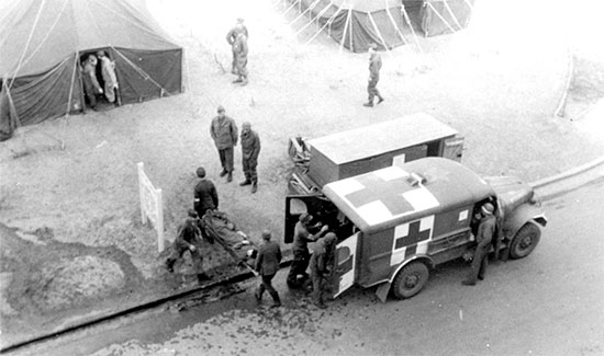 A patient arrives at the 25th General Hospital, Tongres, Belgium. The soldier is transferred from the 3/4-ton ambulance to the Receiving by PW litter bearers.