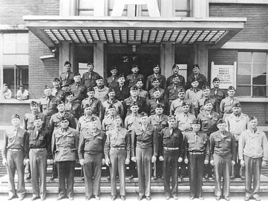 Group of Officers of the 25th General Hospital, in front of the main entrance to one of the military barracks occuped by the unit at Tongres, Belgium.
