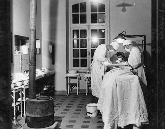 Operating room in action at Baccarat, France, where the 27th Evacuation Hospital. The organization occupied the Caserne Ladmirault where they remained from November 25 to December 17, 1944. Courtesy UIC.