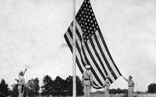 "MPs hoist the ""Stars and Stripes"" above Camp McCain (birthplace of the 623d Medical Clearing Company) during the summer of 1942."