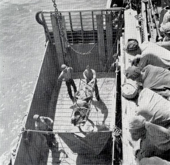 American casualty being loaded aboard a transport vessel in Leyte harbor, 20 October 1944.