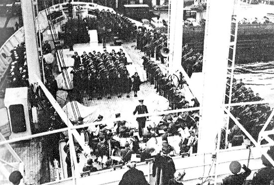 Partial view of the official Commissioning, taken 16 March 1945. Foredeck USAHS Louis A. Milne; the band is playing the national anthem while all personnel stand at attention and salute.