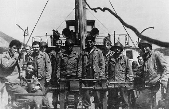 Picture illustrating some personnel of the 60th Field Hospital aboard a ship. This could well be the Moselle or the Rhine rivers. The person identified by the arrow left, is Louis Loffredo, 32905282.