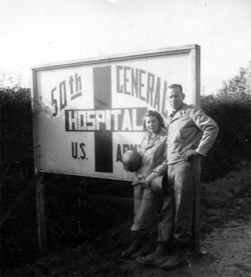 First Lieutenant Frances Cardozo Jones and her husband Earl pose for the camera in front of the 50th General Hospital's sign in Carentan, France.
