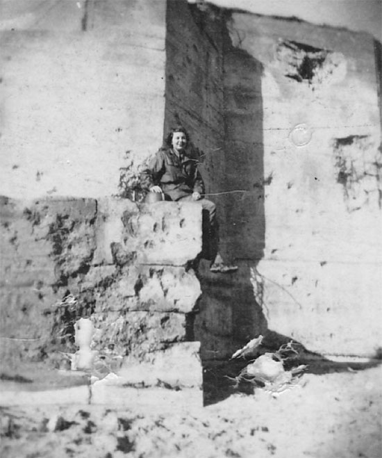 Lieutenant Jones pictured sitting on a partially-destroyed concrete bunker on Utah Beach, July 1944.